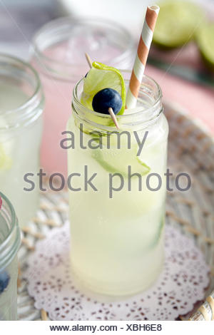 Iced fresh fruit drinks in glass jars with drinking straw - Stock Photo