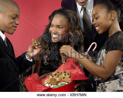 Mother offering children gingerbread men - Stock Photo
