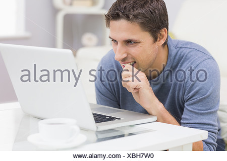 Thoughtful young man using laptop in living room - Stock Photo
