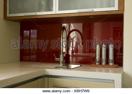 Chrome pepper and salt mills beside chrome tap at miniature sink - Stock Photo