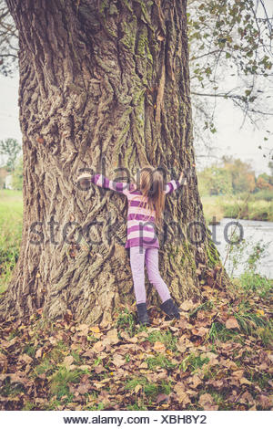 Little girl hugging old tree - Stock Photo