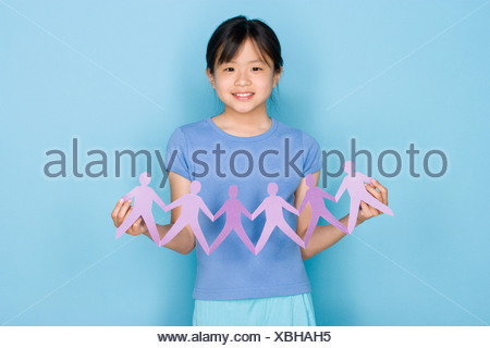 Studio shot portrait of teenage girl holding paper chain, waist up - Stock Photo