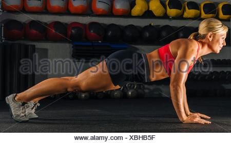 Young woman doing push ups in gym - Stock Photo