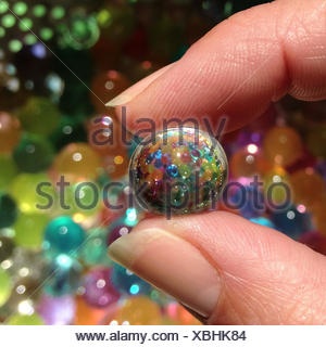 Woman's hand holding a marble - Stock Photo