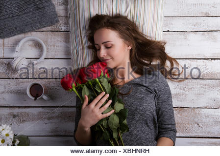 Happy young woman lying on the floor smelling red roses - Stock Photo