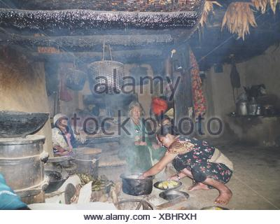 Family cooking dinner in their house in a mountain village, Nepal - Stock Photo