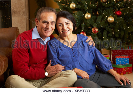 Senior Couple In Front Of Christmas Tree - Stock Photo