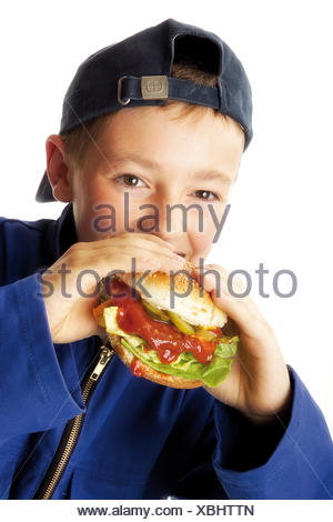 Young boy wearing blue overalls biting into a hamburger - Stock Photo
