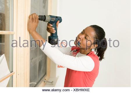 Woman using a power drill on windowsill - Stock Photo