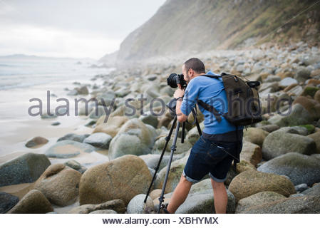 Spain, Valdovino, photographer on the beach with tripod and camera - Stock Photo