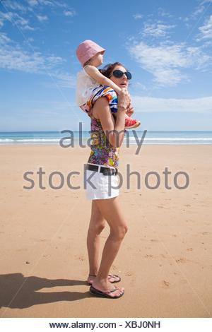summer family of two years old blonde baby with pink hat white shirt and colorful trousers carrying on shoulders or shouldering of woman mother black - Stock Photo