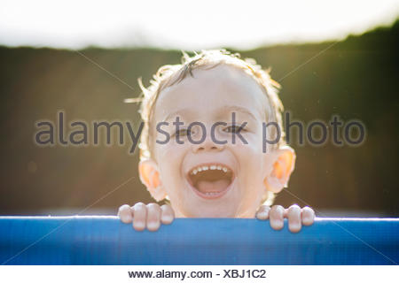 Portrait of laughing little boy at backlight - Stock Photo