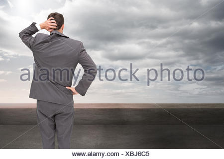 Composite image of young businessman standing back to camera scratching his head - Stock Photo