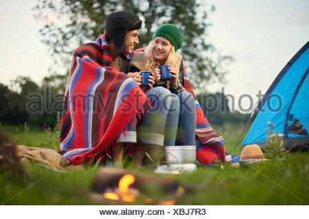 Young camping couple sitting by campfire with cup of tea - Stock Photo