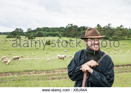 Portrait of farmer in field, smiling - Stock Photo
