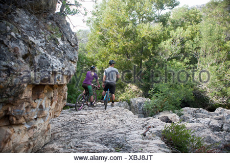 Young couple resting on mountain bikes on rock - Stock Photo