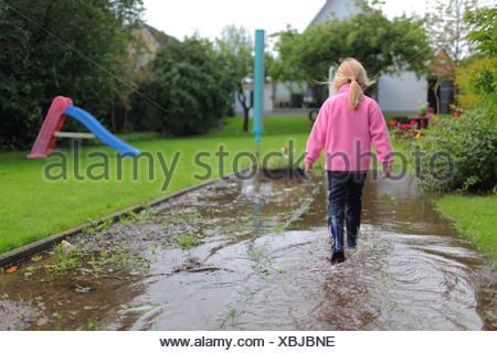 Handewitt, Germany, a girl runs in rubber boots through an over flooded garden - Stock Photo