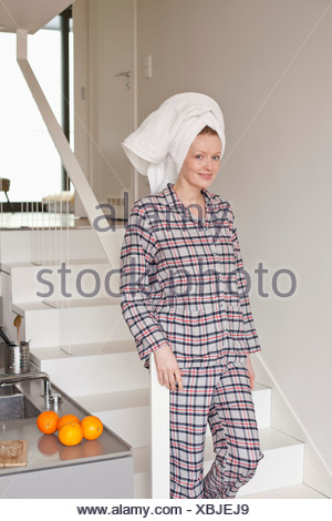 Woman with hair wrapped in towel standing on staircase, portrait - Stock Photo