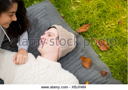 Young couple lying on rug, man wearing knit hat - Stock Photo