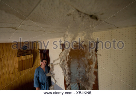 A man discovers a leak in the ceiling. - Stock Photo