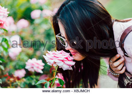 Close-Up Of Young Woman Smelling Pink Flower - Stock Photo
