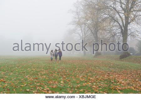 Three young girls walking through field in autumn - Stock Photo