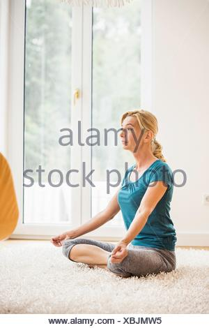 Mature woman practicing yoga lotus position on living room floor - Stock Photo