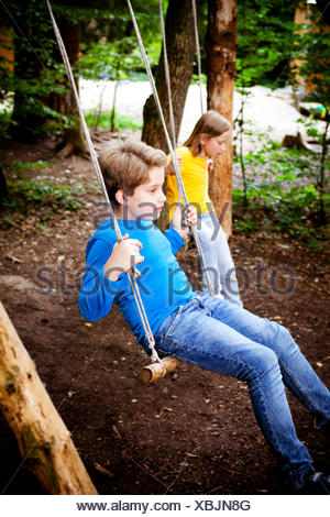 Children playing on swing in forest camp, Munich, Bavaria, Germany - Stock Photo