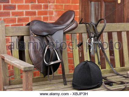Horse saddle, reins and helmet on bench - Stock Photo