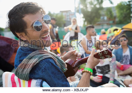 Portrait enthusiastic young man playing ukulele at summer music festival campsite - Stock Photo