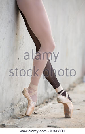 Ballerina feet close-up on a background of textured concrete wal - Stock Photo