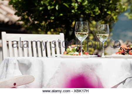 Italy, South Tyrol, Laid table, with mixed salad on plates and two glasses with white wine - Stock Photo