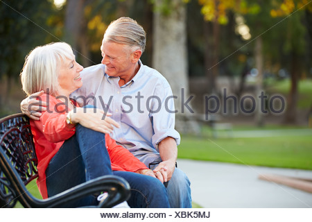 Mature Romantic Couple Sitting On Park Bench Together - Stock Photo
