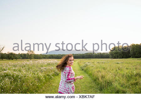 Woman running along a path in a meadow, looking over her shoulder. - Stock Photo