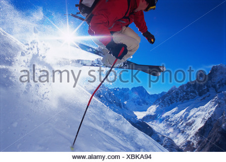 Skier jumping on snowy hill (lens flare) - Stock Photo