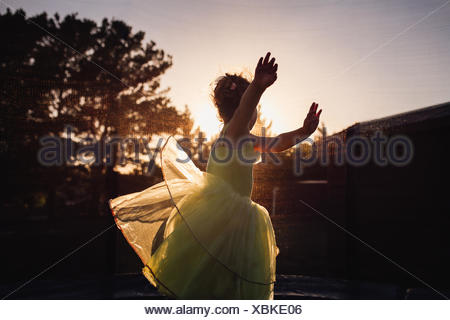 Girl spinning around in garden at sunset - Stock Photo