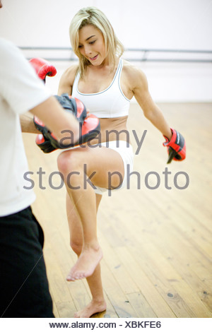 Young woman kickboxing with personal trainer - Stock Photo