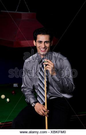 Man applying chalk to cue stick - Stock Photo