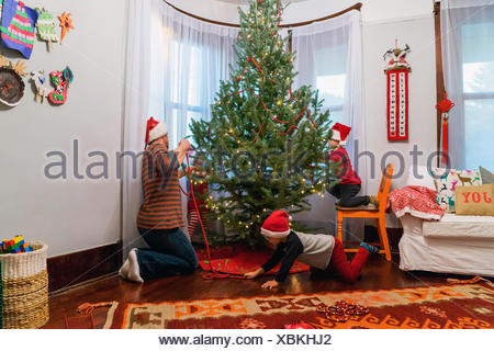 Father and three children decorating a Christmas tree - Stock Photo