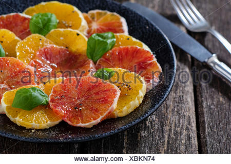 Orange salad and blood orange salad on dark plate - Stock Photo