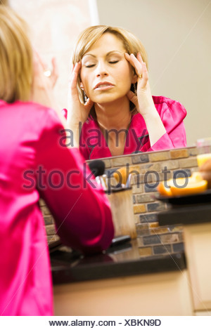 Woman massaging her head in mirror - Stock Photo