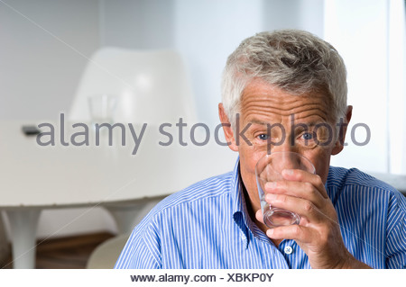 Senior man drinking a glass of water - Stock Photo