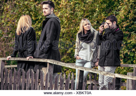Group of friends standing on wooden bridge - Stock Photo