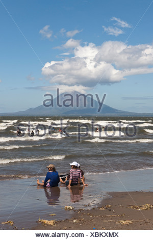 People sitting on the shallow shore of Lago de Nicaragua with the volcanic island of Ometepe and the stratovolcano Volcán - Stock Photo