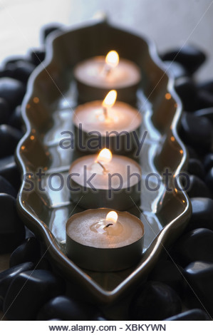 Close-up of four aromatherapy candles burning in a tray with black pebbles - Stock Photo