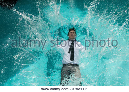 Young Man In Clothes Falling Into Swimming Pool Stock