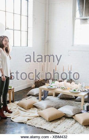 A woman in a room decorated for a party, with lit candles and a table laid for a meal. - Stock Photo