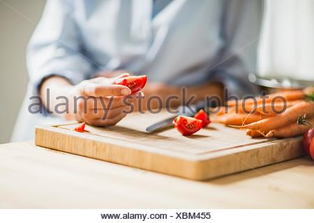 Cropped shot of full term pregnancy young woman slicing tomato in kitchen - Stock Photo