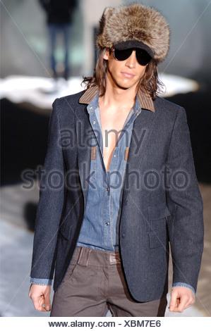 Iceberg Menswear Milan A W Brunette male long hair wearing a grey pin striped blazer over a denim brown trim button down shirt - Stock Photo