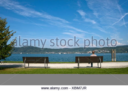Woman wearing a headscarf sitting on a bench on the shore of Lake Constance, Bodman, Baden-Wuerttemberg - Stock Photo